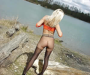 Blonde girl in black seamless pantyhose on a riverside