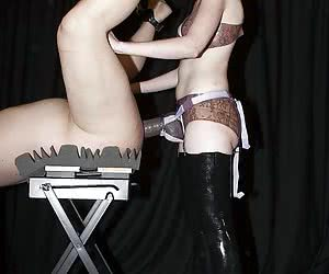 Mistress in latex boots penetrates male slave with a big strapon and makes him cum on himself