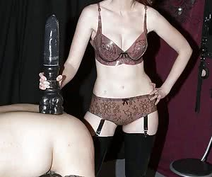 Mistress in latex lingerie penetrates male slave using very very big dildo