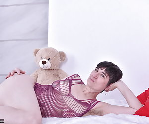 Posing on the bed with my Teddy Bear.Me in a purple Outfit.He looks at me as I undress me.