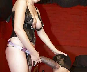 Cute Mistress posing with a huge strapon and forces male slave to suck it and to take it from behind
