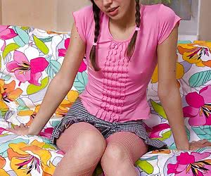 Long-legged young beauty in pink top and pantyhose exposes her private parts