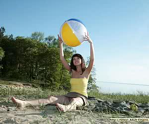 Big-boobed young beauty playing with a ball in the nude on the sand