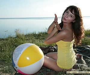 Big breasted young beauty getting naked and playing with a big ball