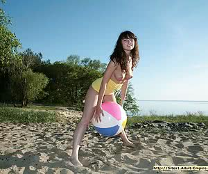 Busty young girlie playing in the nude with a big ball at the lakeside
