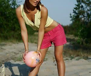Cute redhead playing with a ball and getting out of her clothes