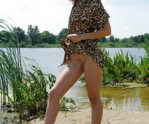 Dark-haired hottie getting out of all her clothes at the lakeside