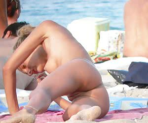 Female nudists sunning every inch of their bodies on a sandy beach