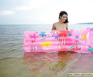 Gorgeous young brunette luxuriating nude in the warm water at the wild beach
