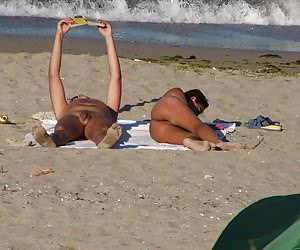 Two nudists spending their vacation time on the wild sandy beach