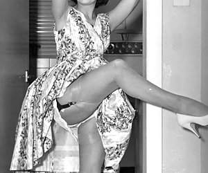 Passionate gal in old-fashioned dress raises her legs to let you take a glance at her retro lingerie