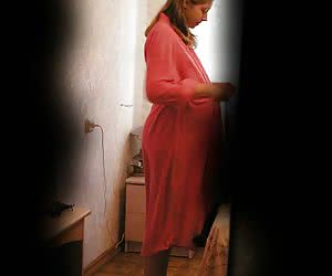 Lovely pregnant woman photographed through the keyhole in the moment of changing her dress